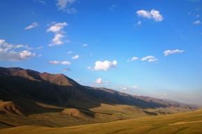 Parcul Național Issyk Kul în culorile apusului, cu munții având efect de pled din catifea ce îi acoperă.